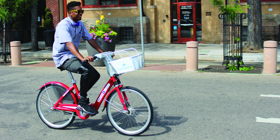 A stylish man rides a B-cycle