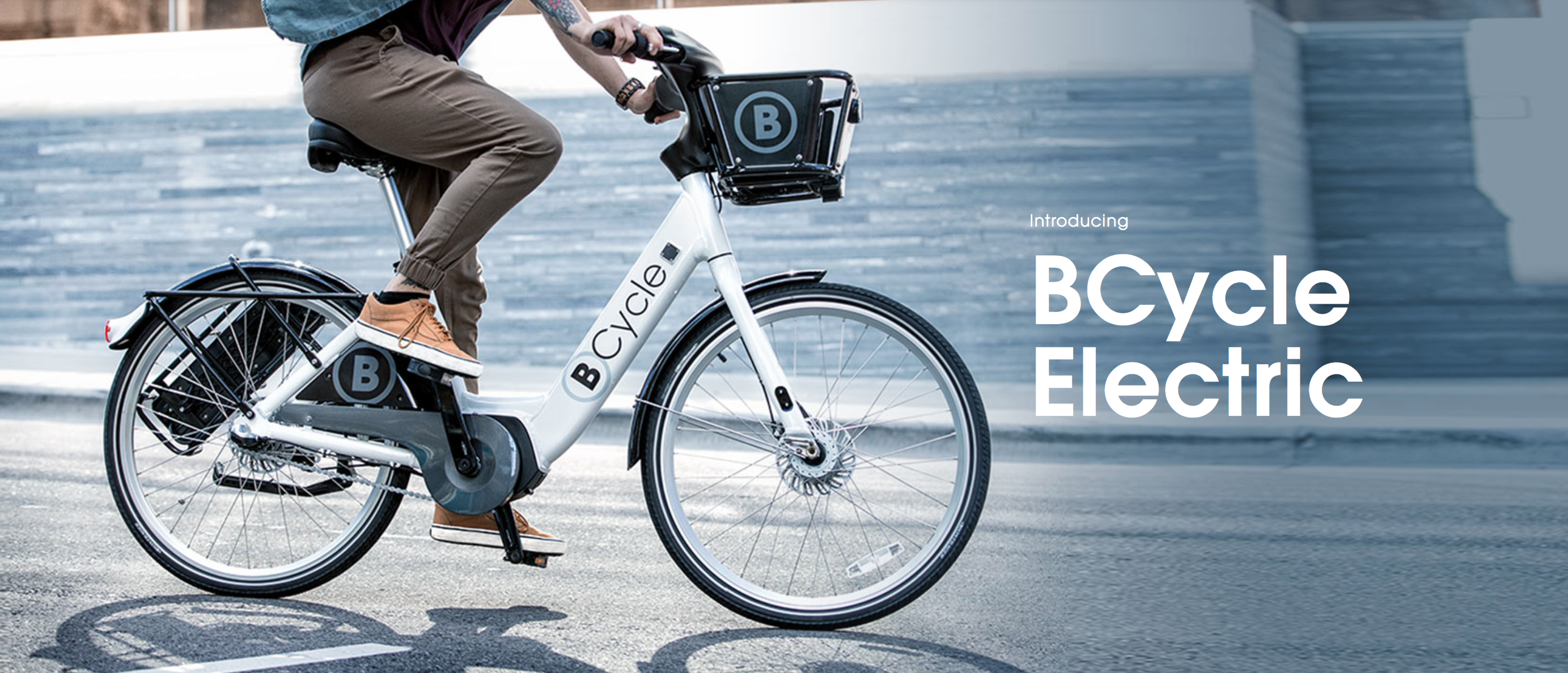 A Boulder B-cycle rider next to a B-station